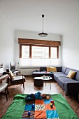 Narrow interior with sofa combination and baby playing with toy cups on play mat