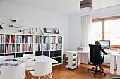 Weiss möbliertes Architekturbüro mit Frau an Computerarbeitstisch, Besprechungstisch und Modellen auf halbhoher Regalwand
