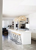 Barstools with metal frames at white, free-standing kitchen counter below wicker pendant lamps in designer apartment