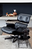 Charles Eames lounge chair with black leather cover and side table in front of concrete shelf
