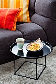 Snacks on black side table and comfortable sofa with striped scatter cushions