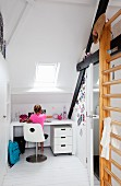 White, child's bedroom in attic - child sitting on swivel chair at fitted desk below sloping ceiling