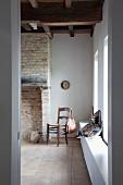 View through open door of wooden chair next to old, brick open fireplace