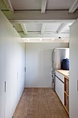 Clearly laid out utility room with modern stainless steel appliances and practical fitted cupboards