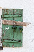 Hook rack made from old driftwood with posies of forget-me-nots and heart ornament hanging on vintage window shutter