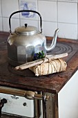 Lovingly wrapped gift decorated with driftwood and forget-me-nots on nostalgic cooker