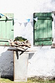 Collection of driftwood pieces arranged as planter on rusty zinc container against farmhouse facade
