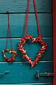Heart-shaped wreaths of rosehips hanging on petrol blue exterior door