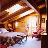 Double bed below skylight and antique armchair next to balcony door in wooden house