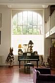 Klavierflügel und antiquarisches Schaukelpferd vor hohem Rundbogenfenster in herrschaftlichem Raum mit Galerie