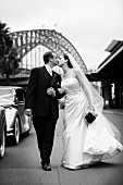 Bride wearing long white dress and groom in black suit kissing whilst walking down the street (black and white photo)