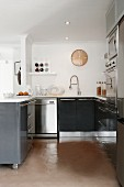 Open-plan kitchen in shades of grey and stainless steel; retro clock above sink