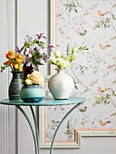 Metal table with an assortment of flower arrangements in vases in front of floral wallpaper