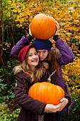 Two girls holding giant pumpkins in a garden