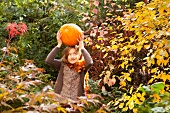 Girl balancing a giant pumpkin on her head