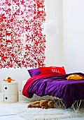 Curtain with red pattern of flowers and animals and bold purple bed linen