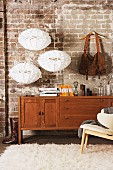Vintage bag hanging from wooden coat hanger and three, white, designer pendant lamps decorating old brick wall