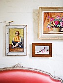 Framed pictures on wall above partially visible backrest of couch with red leather cover and Rococo wooden frame