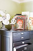 Vintage fans and collection of pictures on light grey chest of drawers