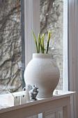 Weisser Tontopf mit spriessenden Blumen auf Fensterbank und Blick auf berankte Aussenwand