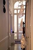Abgehängte Lichterkette mit Papierschirmen in herrschaftlichem Treppenhaus mit Rundbogenfenster