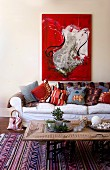 Bright red modern painting above country-house sofa with collection of cheerful cushions; coffee table upcycled from carved, repurposed wardrobe door