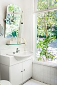 Simple, white washstand and angled mirror next to large window with view of garden