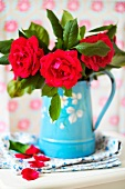 Red roses in a blue enamel pitcher