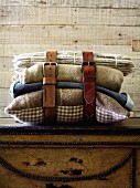 Leather belts around stack of blankets and cushions in rustic ambiance