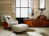 White armchair and matching footstool on animal-skin rug on floor next to rustic bench with leather seat cushion below window in wooden wall