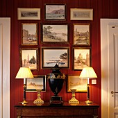 Urn-shaped vase flanked by table lamps with pleated fabric lampshades on antique cabinet below gallery of framed pictures
