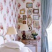 Corner of bedroom with table lamps and collection of pictures on wall covered in floral fabric