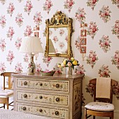 Table lamp with pleated fabric lampshade on painted chest of drawers below gilt-framed mirror on floral wallpaper