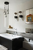 Fitted bathtub with black, stone cladding below potted plants on masonry wall brackets and next to washstand and mirrored cabinet