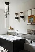 Eingebaute Badewanne mit schwarzen Steinseitenwänden unter gemauerten Wandkonsolen mit Blumentöpfen, seitlich Waschtisch mit Spiegelschrank