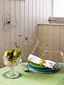 Small fruit bowl and a place setting on a table with a green tablecloth