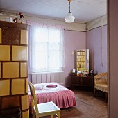Double bed with pink counterpane opposite dressing table with tall mirror in pink-painted bedroom