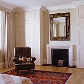 Elegant mirror above fireplace and English lounge chair in front of fitted wardrobe with panelled doors in bedroom