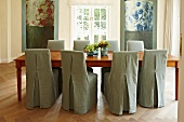 Chairs with simple, light gray covers at a long wooden table in a modern dining room with traditional flair