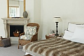 Animal skin bedspread on a double bead and rattan chair in front of an open, classic fireplace in a bedroom with traditional flair