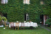 Set table in front of an house facade covered with wild grapevines