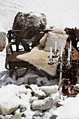 Wooden bench with an animal skin and pillows and candlesticks in the snow