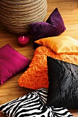 Colorful decorative pillows and a glass candle holder on parquet floor