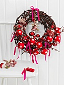 Natural grass wreath with red and white Christmas decorations on the back of a chair