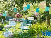 Tisch mit Sommerstrauss und Lampions unter dem Apfelbaum