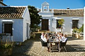 Group of adults sitting at long table in cobbled courtyard of Mediterranean country house