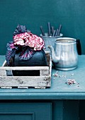 Still-life arrangement of silver teapot & bouquet of carnations & rex begonia leaves in vase