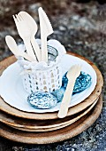 Wooden cutlery in glass jar covered in lace doily and pebbles on plate on stack of wooden boards