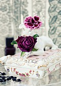 Purple floribunda rose & purple carnation on antique china casket topped with dog figurine