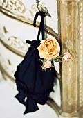 Pompadour mit apricotfarbener Rosenblüte an antiker Kommode hängend
